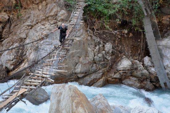 Eric dans l'exercice périlleux du franchissement d'une passerelle de fortune au-dessus des eaux bouillonnantes de la Ghunsa khola